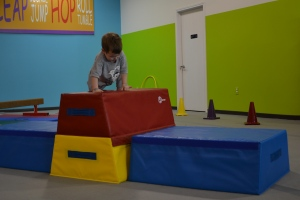 He was a natural already doing forward rolls, handstands on the wall, swinging on the bar and walking on the balance beam. But his favourite thing to do was big jumps off the mats!